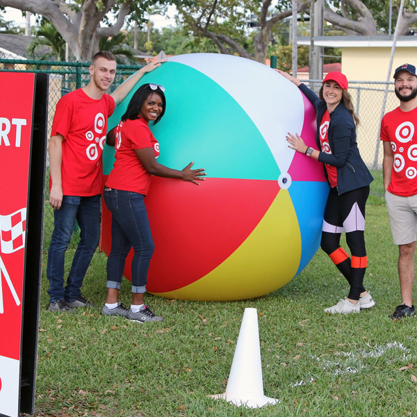 At the Play Everywhere Tour, powered by Target, volunteers pose with a giant inflatable beach ball.