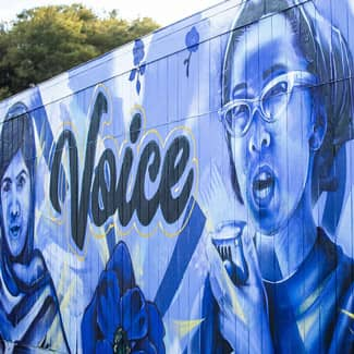Within the mural, a portrait of Malala Yousafzai nxt to the word Voice.