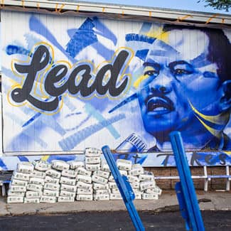 A painted bust of Dr. Martin Luther King, Jr next to the word Lead