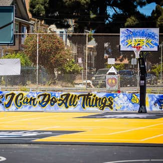 A mural around the multi-sport court says I can do all things