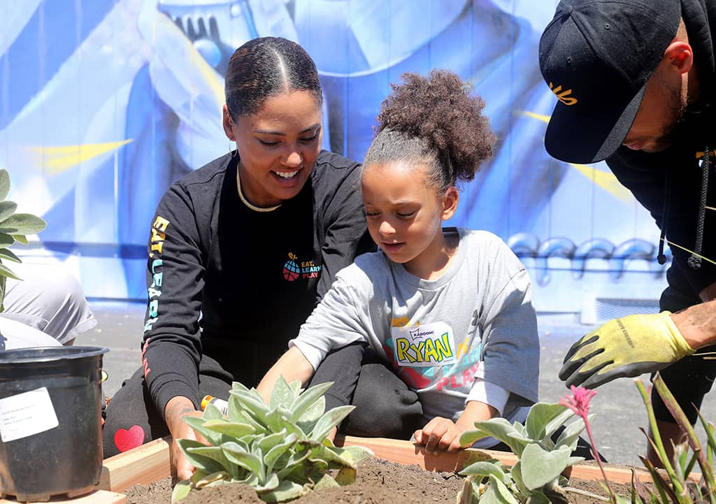 Ayesha Curry and Ryan Curry plant in the garden